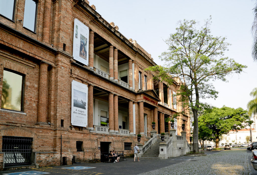 "Side facade of the Pinacoteca, all in apparent bricks. Large building with 2 floors with very high ceilings. On both floors, in the center, the walls are recessed forming a terrace supported by 3 pairs of columns. On the lower floor, a staircase in gray concrete with access on both sides, lead to a large entrance door, flanked by two other columns and, at the top, the word ""PINACOTECA"" is written in red."
