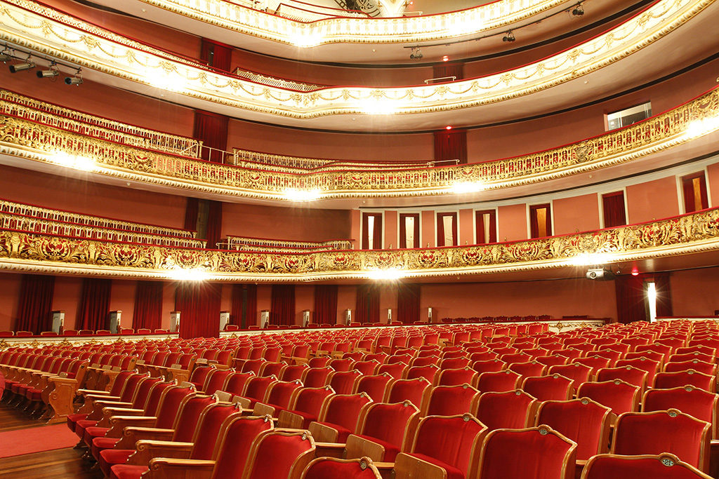 Image of the inner part of the auditorium. Below, hundreds of armchairs in red velvet upholstery, arranged in the audience in several rows. On the side, cabins with red and gold armchairs, salmon-colored walls and access doors covered by red curtains. Above, 3 mezzanines with cabins like the ones below, protected by railings, richly worked in gold and red handrails. Several sets of strong white light reflectors, attached to the base of the grids.