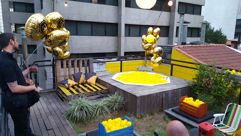 Terrace with rustic wooden floors. To the left, a man in black clothes holds several golden balloons; bench made with wooden slats, yellow seat with 3 blue and yellow cushions. In the center, small garden with foliage and shrubs; Rustic wooden raised deck with an octagonal hot tub filled with yellow polka dots. To the right, several golden balloons attached to a side railing. Below, 2 boxes, one blue another red, full of yellow balls, beach chair with colorful stripes. In the background, part of the side of a yellow house with reddish-brown tiles and 3 metal chimneys; part of the side of a gray building with wide horizontal windows from end to end.