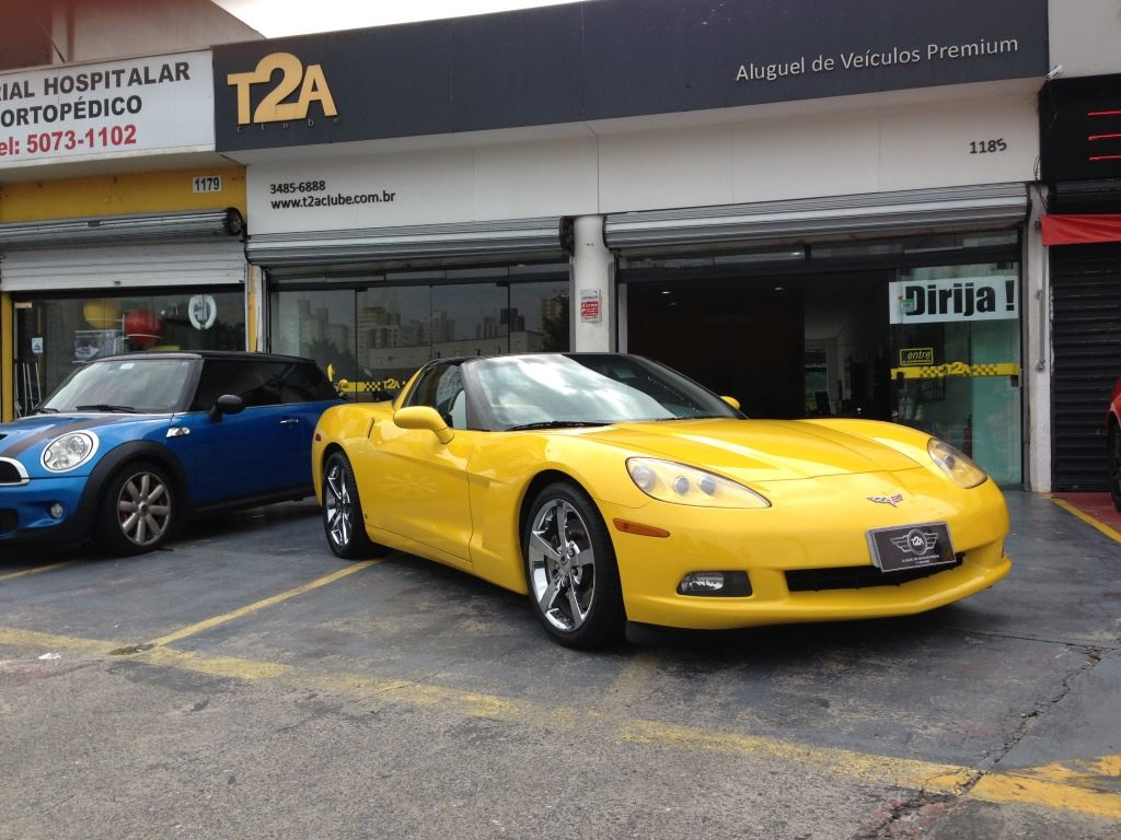 """Featured image of 2 luxury cars. On the left, 1 Blue Mini Cooper with black top. On the right, a yellow, convertible Corvette. Behind, the facade of a store with two large windows. On the top, on a black background, on the left side is written in large yellow letters """"T2A"""" and, on the right, in smaller white letters """"Premium Vehicle Rent""""."""