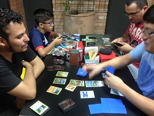 Rectangular table in black color. On it, several card games and board. On the left side, a man in a black T-shirt plays cards and a boy in a blue and black T-shirt looks closely at the phone in one hand. On the right side, man in blue T-shirt plays cards, another man in red T-shirt manipulates board game. In the background, black wall with broad band of light bricks and flower box attached to the wall.