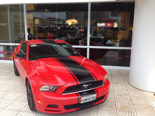Featured picture, a red Ford Mustang with black stripes on the hood and the roof. Behind, facade of a store with a large window.