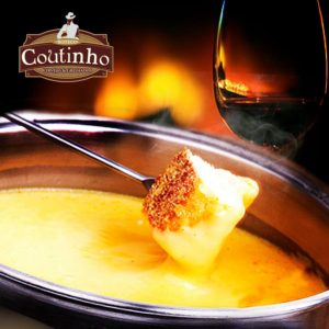 "Image in close up. Small silver metal pan containing melted cheese (cheese fondue). Leaning on the edge, above the melted cheese a silver metal skewer with a small piece of bread on the tip. Behind, on the right side, a crystal goblet with some red wine. To the left, at the top, the logo of the bar brings the word ""Coutinho"" in white letters on a brown stall. In the background, the blurred image of the fire in a fireplace."