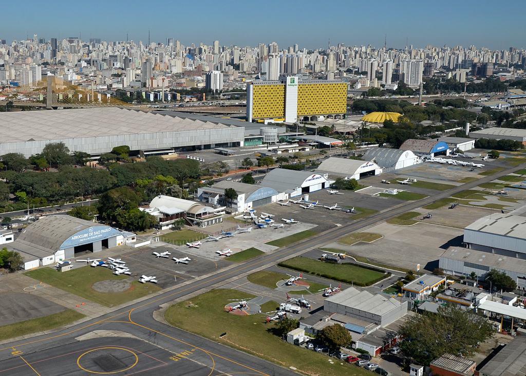 Aerial photography. In the first plan, parking area with several small airplanes, helicopters and hangars. In the 2nd plan, on the left, the Anhembi Exhibition Pavilion and, on the right, the yellow side of the Holiday Inn Anhembi Hotel. In the background, city skyline.