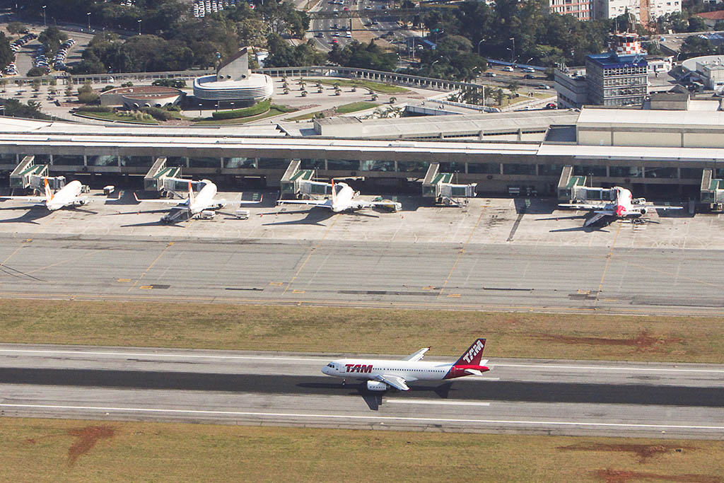 Aerial photography. In the foreground, TAM jet running down the runway. In the background, part of one of the terminals with 4 jets parked on the fingers.