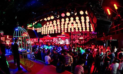 Grande salão com centenas de pessoas dançando e conversando. À esquerda, um DJ trabalha sobre um palco. No teto, uma grande armação com luzes multicoloridas e grandes caixas de som nas laterais.