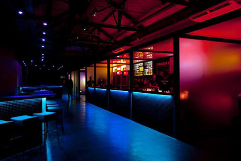 2 rooms separated by a wall with large windows. On the left side, a very long empty hall, very dark and lit by blue lights. On the right side, bar with several people, all lit by red lights and oranges.
