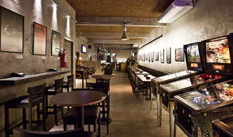 Very long hall, with light brown walls, where several photographs are placed. Several wooden tables and chairs and some pinball machines are on site.