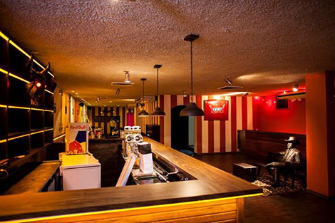 Small place with soft lights. On the left side, a light wooden balcony with a thin tube of yellow light underneath. A bar with several dark shelves filled with bottles of drinks. On the right side, empty hall with multicolored walls.