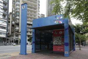 """Estrutura retangular em alvenaria azul claro, sobre uma calçada. Fachada toda aberta apresenta no canto superior direito a Marca São Paulo. Na entrada, painel vermelho retangular na vertical, expõe um mapa tátil dos arredores. No lado de fora, à esquerda, totem azul escuro com as palavras """"Central de Informação Turística"""" escritas na vertical com letras brancas e, no topo, o símbolo internacional representado por um círculo branco com a letra """"i"""" no centro. Atrás e ao fundo, parte de uma rua e vários prédios."""