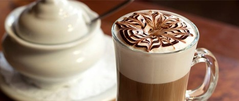 Image in close up. A medium-sized cup, all glass clear and full of coffee with milk. On the surface, on a thick clear foam, a stylized drawing made with fillets of light and dark chocolate. On the left side, a small sugar bowl all white.