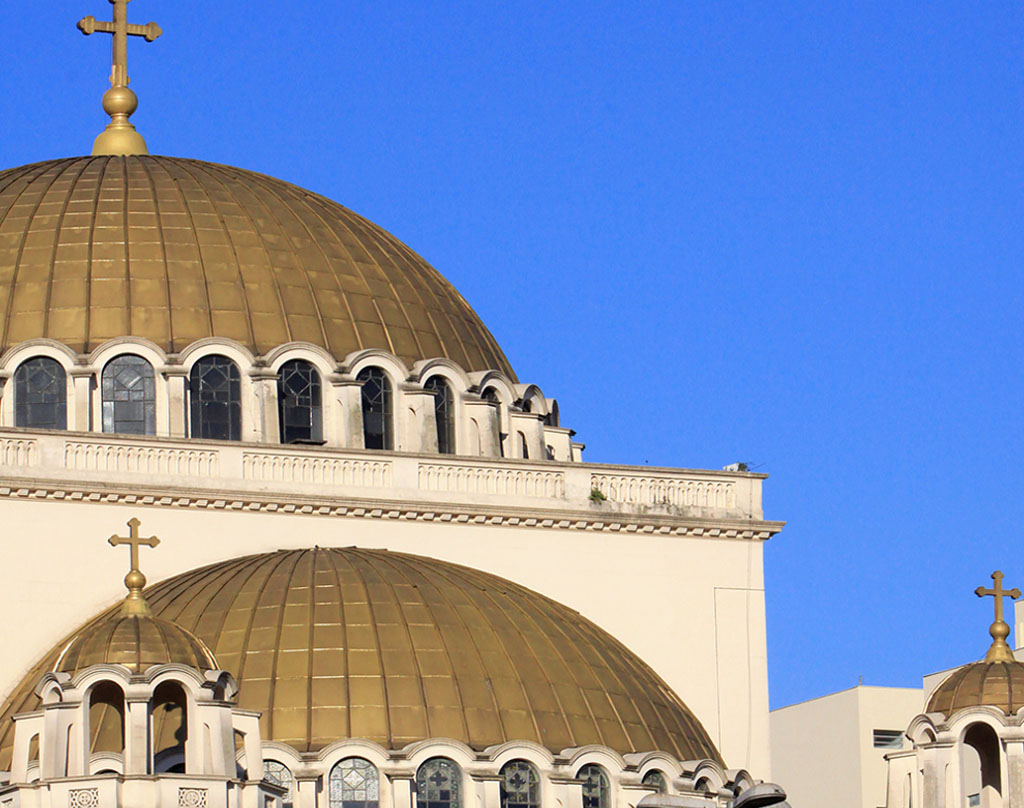 Close-up image of 2 golden domes of the Cathedral. The bottom is a half dome, leaning against a wall and at the base is surrounded by several glass windows on metal frame and rounded top. The main dome is above, has a large cross at the top and, like the bottom, is also surrounded by several windows. All under a very blue sky without clouds.