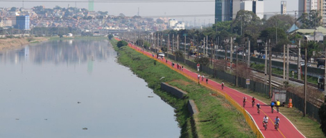 Aerial image. On the left side, the Pinheiros River. On the right bank, a long red-colored cycle path, where several cyclists transit. In the background, on the left bank, hundreds of houses.