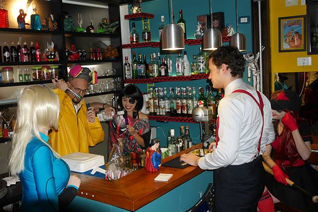 Small bar in the left corner of the place. On the left and bottom walls, several shelves with some bottles of drinks, glasses and some decorative objects. In the center, around a small light brown wooden counter, some people in colorful clothes, inspired by comic book characters, prepare and taste assorted cocktails.
