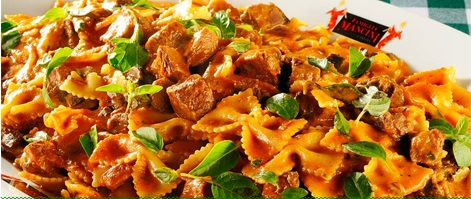 Image in close up. Portion of pasta type Farfalle with tomato sauce, cubes of meat and leaves of basil.