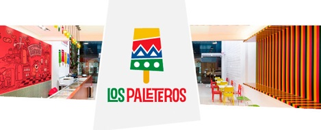 "Stylized drawing of an ice cream with a yellow stripe on top, followed by a red, a zigzag blue stripe, a green with white polka dots and a toothpick placed on the base. Below is written ""LOS"" in green and ""PALATEROS"" in red. The drawing is on a picture of the interior of the ice cream shop."