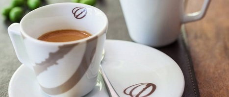 Image in close up. Cup with espresso coffee, all white with two diagonal stripes in dark brown. On the inside edge, the drawing of a small coffee bean. It is on a white saucer with the same design and has a small silver spoon on it.
