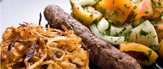 Traditional Arabic cuisine dish with fried onion strips, ground beef skewer, potato salad, tomato and onion.