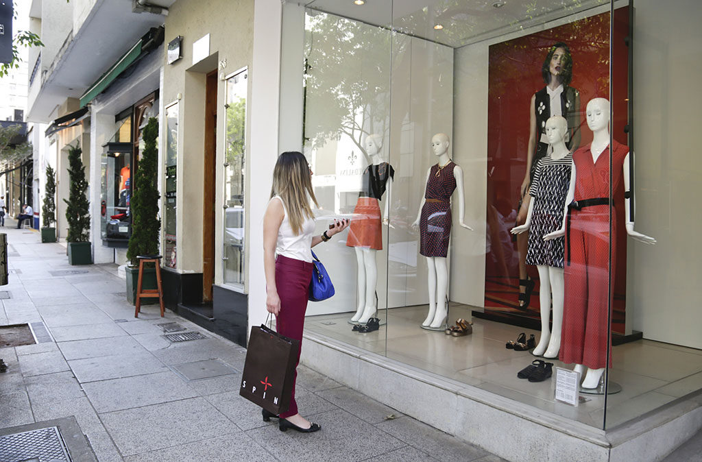 Calçada com várias vitrines. Mulher com sacola de loja na mão observa vitrine de uma loja com 4 manequins vestindo roupas femininas multicoloridas. Na parede do fundo, grande painel com a foto de uma modelo.