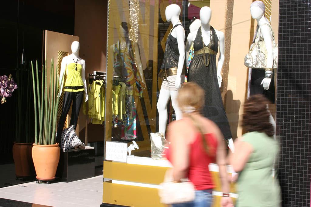 Duas mulheres passando em frente a uma loja, observam uma vitrine com 3 manequins vestindo roupas femininas pretas e douradas. Do lado esquerdo, entrada da loja com um vaso de plantas e, mais atrás, outro manequim veste calça preta e blusa amarela, e uma arara de roupas mais ao fundo.