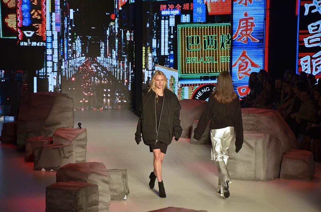 Duas modelos desfilando em uma passarela com piso bege claro. A que está de frente é loira e veste vestido curto e um casaco bem grande, ambos pretos. A que está de costas é morena e veste uma jaqueta preta e uma calça prateada. No fundo, grande painel de led mostra uma grande avenida na China com vários carros e dezenas de placas e outdoors luminosos multicoloridos.