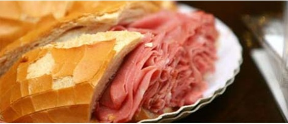 Image in close up. On a paper plate, French bread sandwich with hearty stuffing of mortadella.