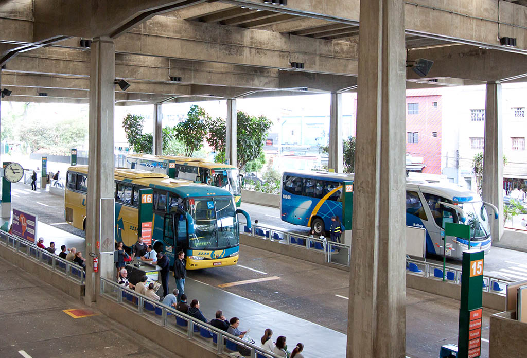 Bus terminal in a concrete structure with a very high ceiling. Two ways side by side with some pretty colorful buses parked. On the sidewalk, several passengers seated, awaiting boarding.