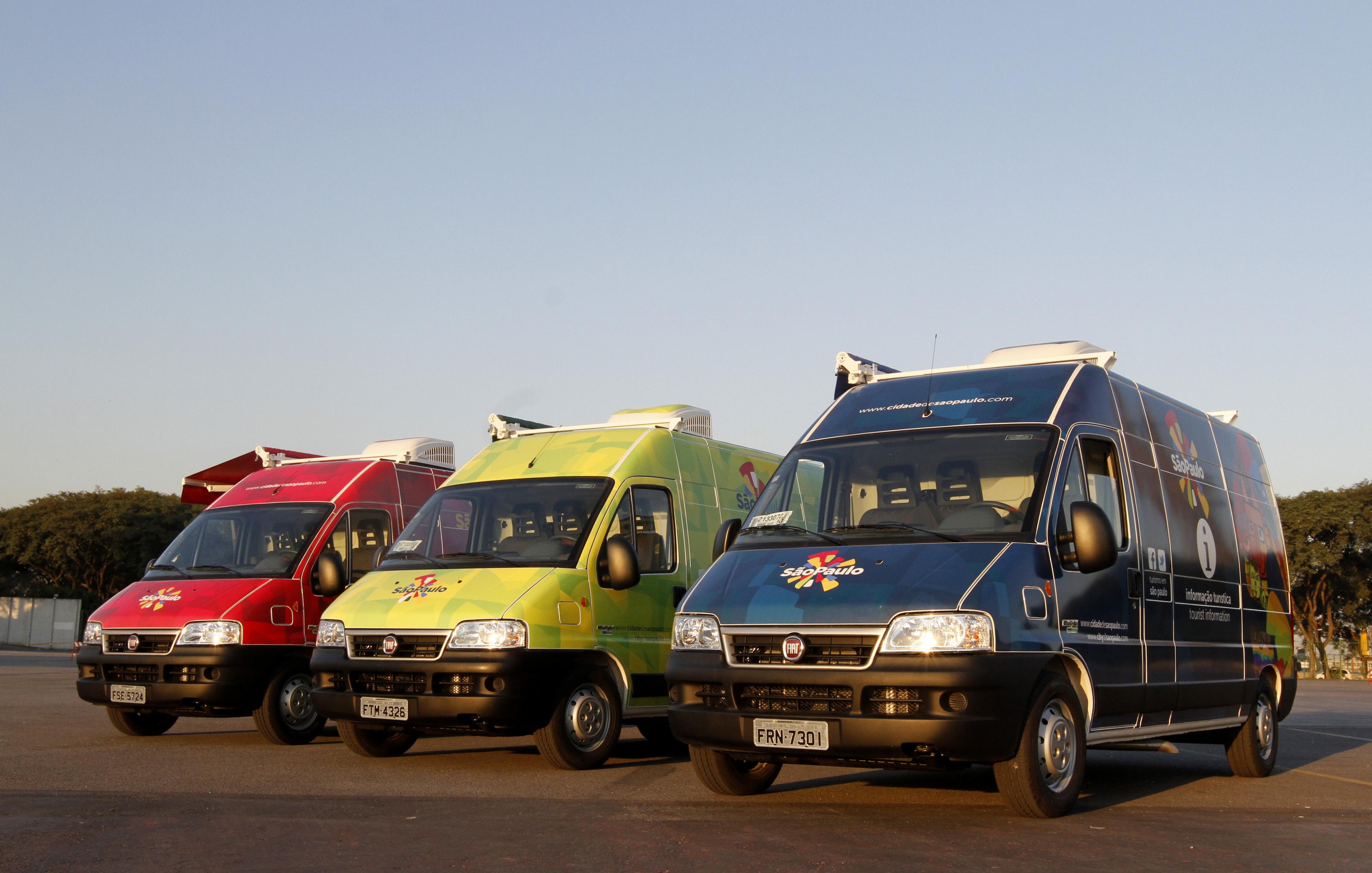 3 Vans, lado a lado. Da esquerda para a direita, a 1ª é vermelha, a 2ª verde claro e a 3ª azul marinho. Todas trazem pintada no capô dianteiro a Marca São Paulo. Acima e ao fundo, um céu azul sem nuvens, ao entardecer.