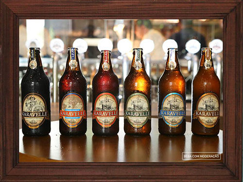 "Picture of a rectangular photo with a dark wooden frame, with 6 medium sized bottles with different types of beers, from golden to caramel, red to black, each with a specific label, all with Nautical motives such as old caravels, nautical charts and sailors, as well as the ""Karavelle"" brand."