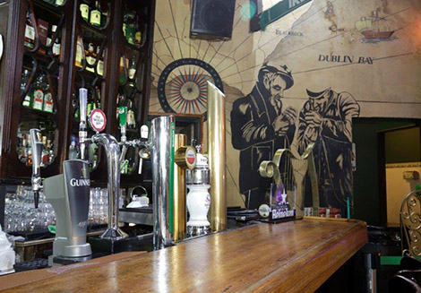 From left to right, assorted beverage bottles on several shelves of a very tall cabinet with glass doors, all in very dark brown wood. Light wood bar counter with 5 draft beer towers, with varying shapes and sizes. On the background wall, painted light beige, drawings that refer to the navigations in the eighteenth century - an old caravel, nautical maps and the figure of 2 sailors smoking a pipe.