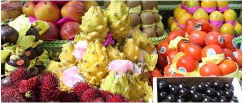 Image in close up. Several fruits grouped as mangoes, lychees, pine cones, oranges, kiwis and persimmons.