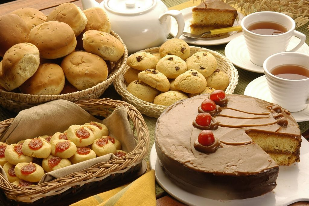 On a wooden table, to the left, a basket with potato loaves and another with biscuits covered with guava jam. In the center, a white tea pot, a basket of cupcakes and a large chocolate covered cake with cherries. To the right, a white plate with a slice of chocolate cake and two white cups full of tea.
