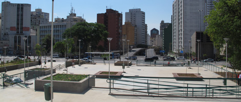 Ample free space with concrete floor. Scattered in this area, small lawns with a young tree in the center, surrounded by squares of concrete and wood benches , measuring 4 square meters each. In the background, several residential and commercial buildings. All under a very blue sky without clouds.