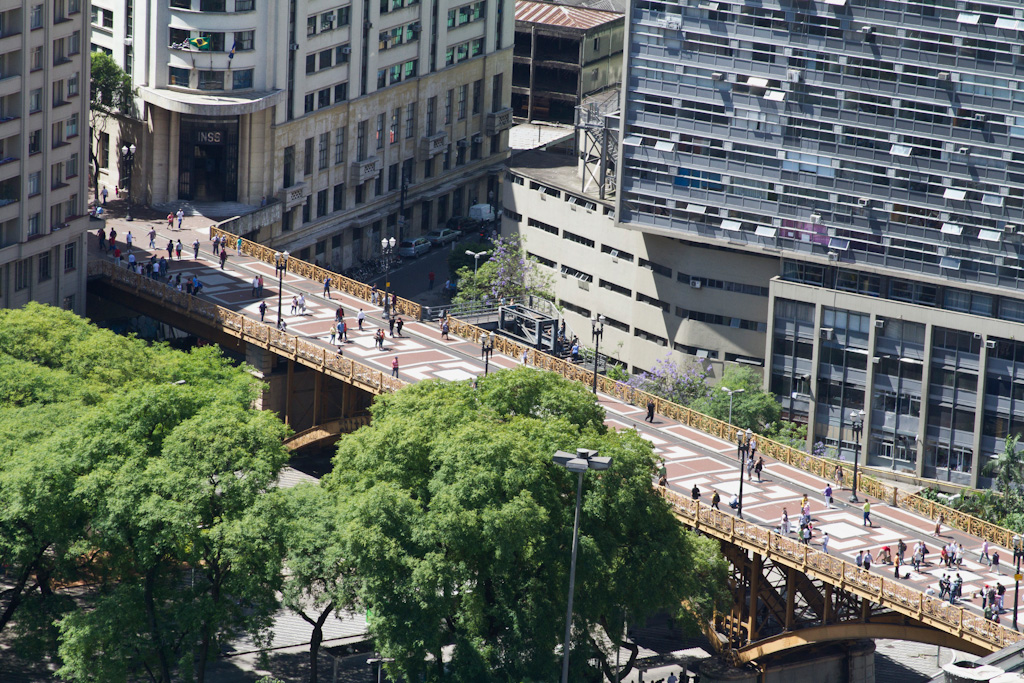 Aerial view. In the center, a viaduct with structure and bars of yellowish steel. The circulation was transformed into a large boardwalk with floor decorated by multicolored geometric shapes, where several people pass. Below is a street with several pedestrians and some vehicles. To the bottom and to the right, part of some commercial buildings. To the left, top of some trees.