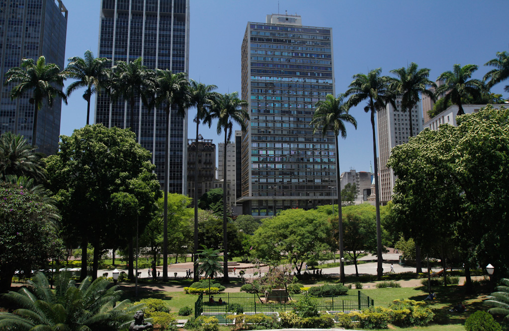 In the first plan, 2 large gardens separated by a promenade. They consist of lawns, flower beds, shrubs, large and medium-sized trees, as well as a set of towering royal palm trees lined up side by side. In the background, some very tall commercial buildings. Everything under a strong sun and a very blue sky without clouds.