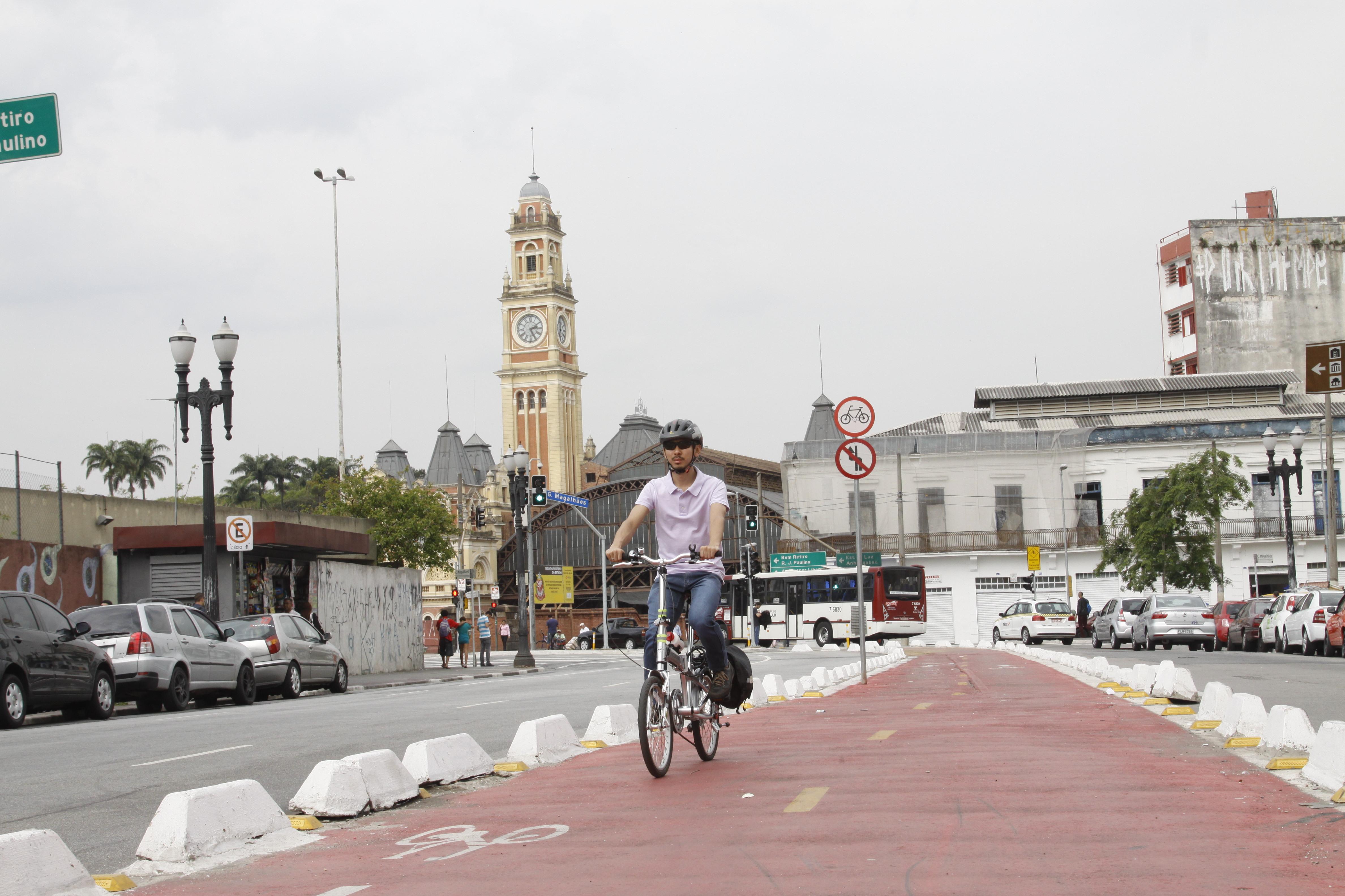 En el primer plano se destaca un ciclista utilizando una ciclofaixa con piso rojo y demarcada en los laterales por peqyenos bloques blancos. A la izquierda, una calle con coches estacionados junto a la calzada. Al fondo ya la izquierda, se destaca la gran torre del reloj, desde la Estação da Luz.