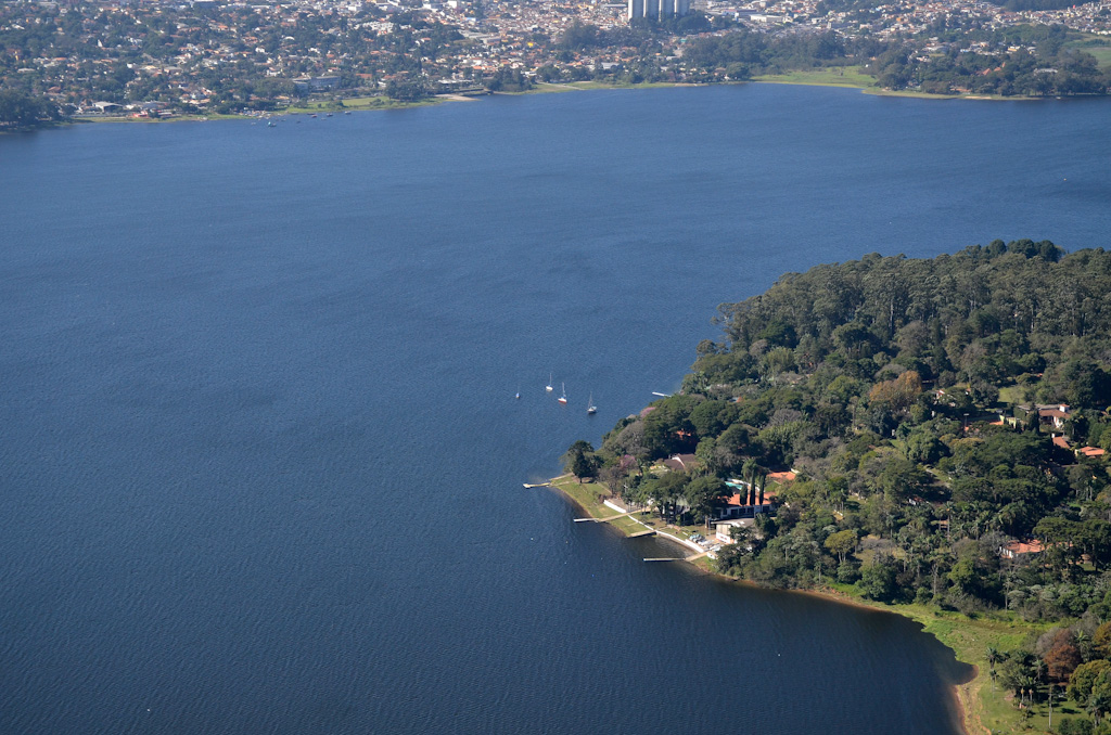 Aerial photo of a large dam. On one of the banks, below and to the right, a closed forest area with some residences inside, one of them right on the water's edge, where there is a small pier. On the other bank, in the background, a large area densely occupied by residences between a few green areas.