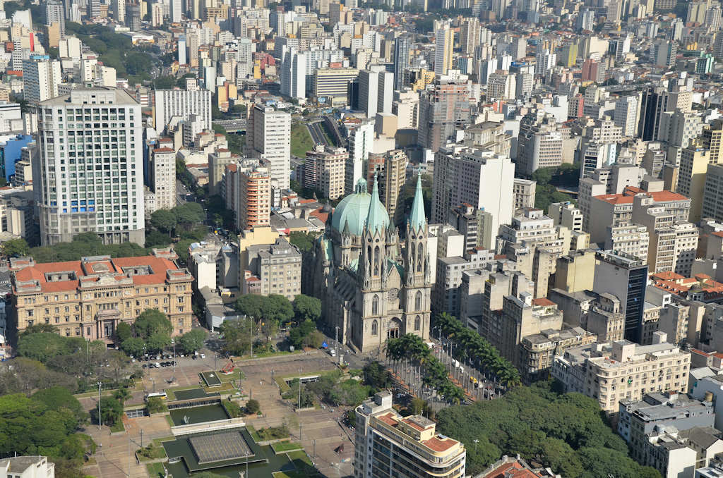 Aerial view. To the left, part of a very large square with concrete floors and several niches of green area of varied sizes, composed of trees of various sizes, scattered all over the place. In the center is a large cathedral with two tall towers at the front and a large dome-shaped roof behind it. To the bottom and to the right, hundreds of commercial buildings.