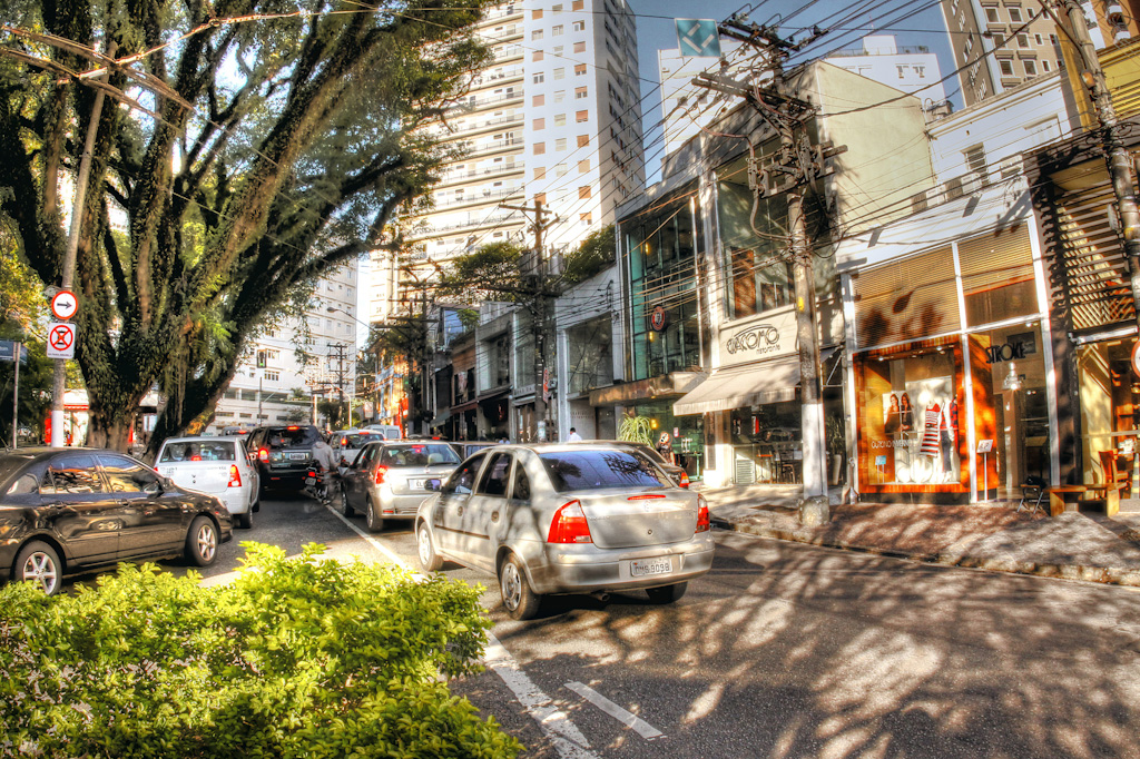 Sunny afternoon. To the left, square with bushes and large trees. In the center, street full of cars, seen from behind. To the right, multicolored facades of various shops. In the background and above, large residential buildings.