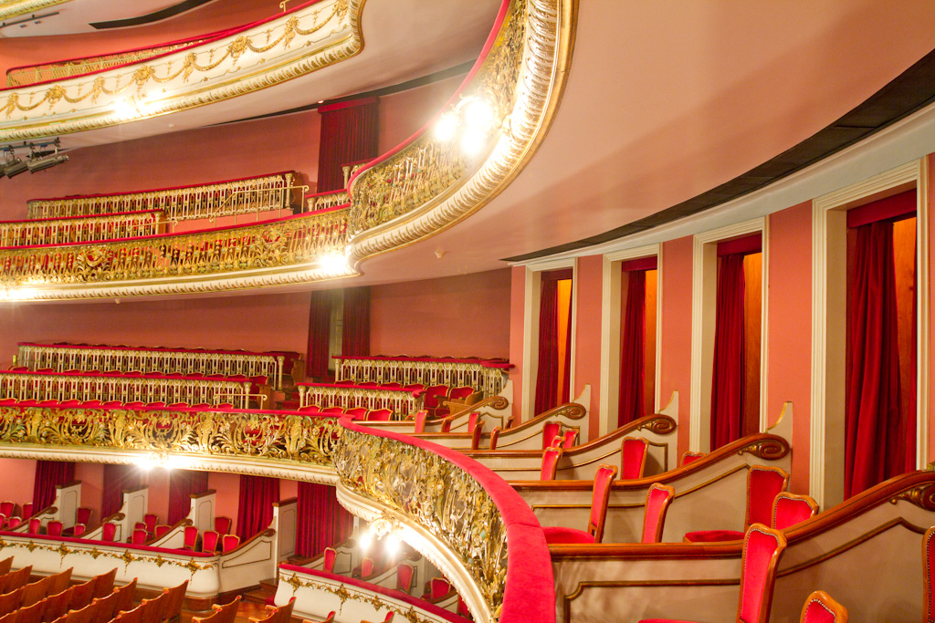 Image of the inner part of the auditorium. Down and left, part of the audience. On the side, theater boxes with red and gold armchairs, salmon-colored walls and access doors covered by red curtains. Above, 3 mezzanines with theater boxes like the ones below, protected by protection grids, richly worked in gold and red handrail. Several sets of strong white light reflectors attached to the base of the protection grids.