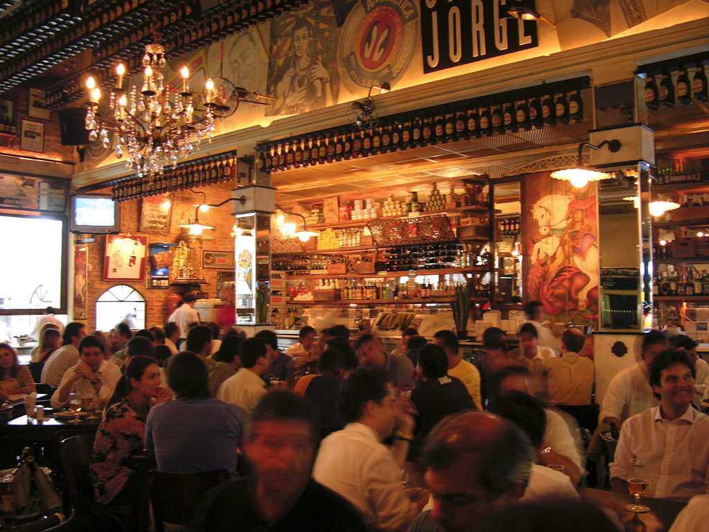 Inside photo of a bar. In the bottom plane, dozens of people, sitting around several tables, drinking and talking. On the ceiling, an old crystal chandelier. To the bottom and to the right, several shelves with several bottles, illuminated by orange lights.