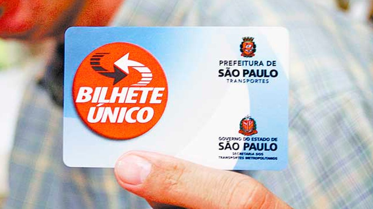 """Close-up image of a Bilhete Único held by 2 fingers of a person. The ticket is the size of a credit card, in light blue color. On the left side, there is a red circle with the words """"BILHETE ÚNICO"""". On the right side, the logo of the City Hall and below the words """"PREFEITURA DE SAO PAULO"""" in black letters."""