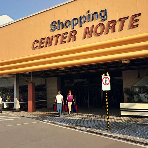 """Fachada de um shopping Center com 2 pisos. No nível da rua, um casal com sacolas de compras sai por uma grande porta de acesso. Na parte superior, uma grande e larga parede amarela possui letreiros luminosos com as palavras """"Shopping"""" em azul escuro acima e """"CENTER NORTE"""" em vermelho, abaixo."""