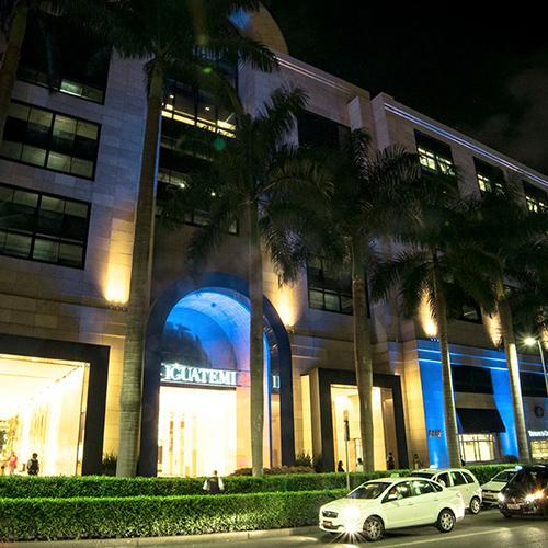 Foto noturna da fachada toda iluminada por luzes coloridas de um shopping Center com 4 andares de altura. No piso térreo, destacam-se grandes vitrines. Na calçada em frente, jardim com várias palmeiras muito altas. Alguns carros passam pela rua.