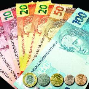 Da direita para esquerda, cédulas de 100, 50, 20 e 10 Reais sobrepostas na vertical em forma da leque. Em baixo, lado a lado, moedas de 5, 10, 25 e 50 Centavos e 1 Real.