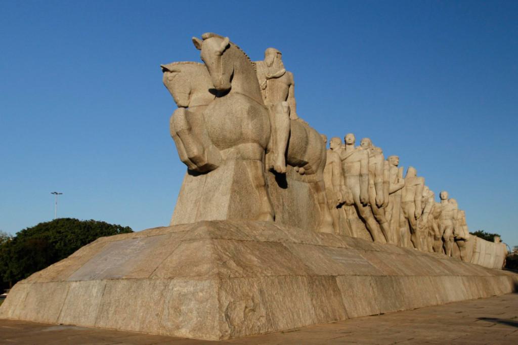 A obra, possui cerca de 11 metros de altura total por 8,40 metros de largura e 43,80 metros de profundidade, toda feita em granito. Da esquerda para direita, à frente 2 homens montados em cavalos lado a lado, Atrás deles, há um grupo de homens que puxam uma canoa, que também é empurrada por trás por mais alguns homens. Acima, um céu muito azul sem nuvens.