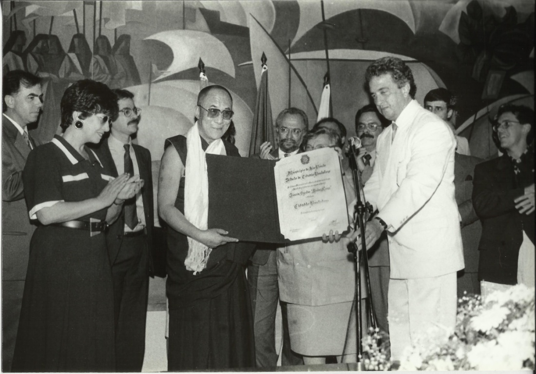 Black and white photo. In the first plan, the Dalai Lama receives the title of Citizen Paulistano from the hands of Mayor Luiza Erundina. Behind, some people applaud. In the background, wall with a large frame containing stylized drawings of Indians in a forest.