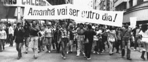 "Black and white photo. A large crowd of people walks down the street, holding up a very wide white band written in black letters the phrase ""Tomorrow is going to be another day!"""