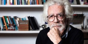 Elderly man with hair and white beard, he rests his face on his left hand. He wears glasses and a black knit. In the background, white wall with two shelves with books, trophies and various other objects.