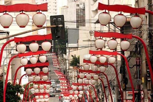 Rua com dezenas de luminárias tradicionais japonesas em ambos os lados. São postes vermelhos curvados no topo sobre a rua, cada um sustentando 3 luminárias brancas arredondadas.